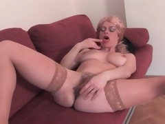 Aged golden-haired strips nude and toys her pussy