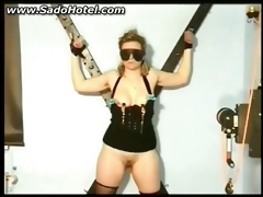 Thrall bound to a wall receives clamps on her nipples and her slit licked by her corporalist S&m